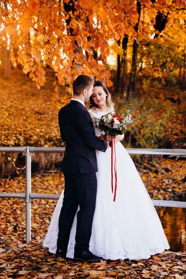 Kāzu foto mirklis pēc kāzu ceremocijas baznīcā. Jaunais pāris un ziedu lietus.